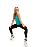 Young woman with slim body. squatting on tiptoes Royalty Free Stock Photos