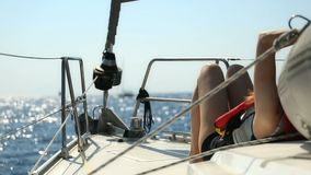 Young woman with slim body sunbathing on the bow of luxury yacht. stock video footage
