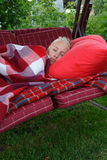 Young woman slip on red pillow covered by red checkered blank Stock Photography