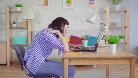 Young woman slouches sitting at a laptop