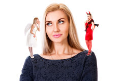 Young woman with small angel and demon on her shoulders Stock Photography