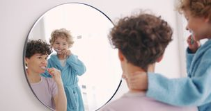 Young woman and small boy brushing teeth in bathroom looking at mirror. Young woman and small boy are brushing teeth in bathroom looking at mirror smiling using stock video footage