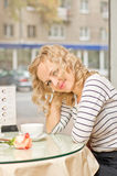 Young woman at small cafe. Attractive young blond woman smiles at small cafe Royalty Free Stock Photos