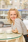 Young woman at small cafe. Attractive young blond woman smiles at small cafe Royalty Free Stock Photo
