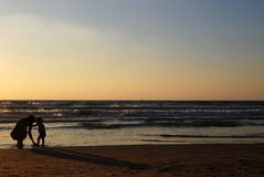 Young woman with small child. On the sea shore on sunset stock image