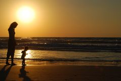 Young woman with small child. On the sea shore on sunset royalty free stock image
