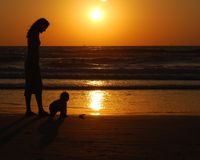 Young woman with small child. On the sea shore on sunset royalty free stock photography