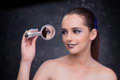 The young woman with small mirror in beauty concept Stock Images