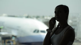 Young woman with smart phone at the airport with airplane on the background. Silhouette of young woman with smart phone at the airport with airplane on the stock video