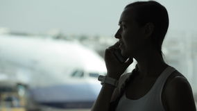 Young woman with smart phone at the airport with airplane on the background. Silhouette of young woman with smart phone at the airport with airplane on the stock footage