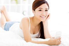 Young woman with smart phone on the bed Royalty Free Stock Images