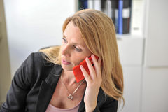 Young woman smart phone office. An attractive young woman at a desktop using her smart phone Royalty Free Stock Photos