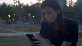 Young woman with smart phone in the park. Young beautiful woman looking in smart phone. Summer evening. Anonymous people walking on the background out of focus stock footage