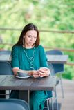 Young woman with smart phone while sitting alone in coffee shop during free time Royalty Free Stock Photos