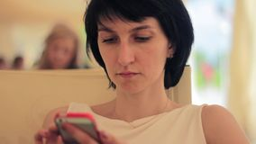 Young woman with smartphone in cafe stock video footage