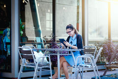 Young woman with smartphone in coffee shop Stock Photos