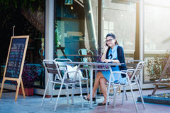 Young woman with smartphone in coffee shop Royalty Free Stock Images