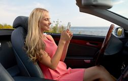 Young woman with smartphone at convertible car Royalty Free Stock Images