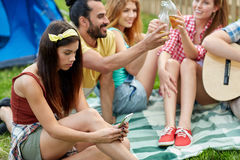 Young woman with smartphone and friends at camping Royalty Free Stock Images