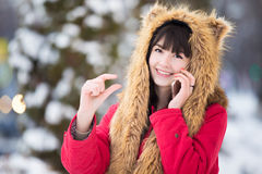 Young woman with smartphone gesturing small amount of something. Portrait of smiling beautiful young woman in red winter coat and funny fur hat posing with phone Stock Photos