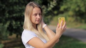 A young woman with a smartphone in her hands is standing in a summer park. Sunny day. A girl makes a selfie stock video