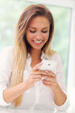 Young woman with smartphone in kitchen Stock Photo