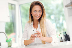 Young woman with smartphone in kitchen Stock Photos