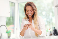Young woman with smartphone in kitchen Stock Images