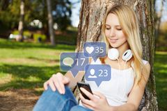 Woman looks at comments on social media. Young woman with smartphone looks at comments on social media Stock Photography