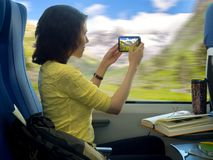 Young woman with smartphone mobile making photos of beautiful scenery during traveling in train near window stock photos