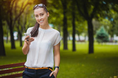 Young Woman with smartphone in the park Royalty Free Stock Images