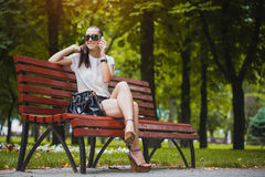 Young Woman with smartphone in the park Stock Photo