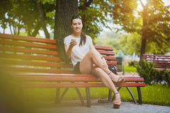 Young Woman with smartphone in the park Royalty Free Stock Image