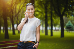 Young Woman with smartphone in the park Royalty Free Stock Photos