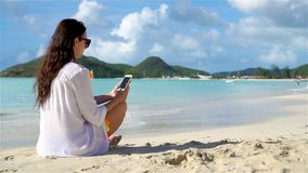 Young woman with phone on tropical beach. Young woman with smartphone on tropical beach stock footage
