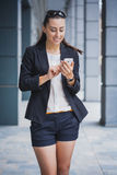 Young Woman with smartphone, walking on the street Royalty Free Stock Image