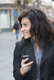 Young Woman with smartphone walking on street Royalty Free Stock Photo