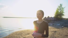 Young woman with smartwatch jogging by sea. Young sporty girl using smart watch on beach at sunset. Sun lens flare