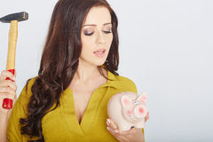 Young woman smashed piggy bank with a hammer Stock Image