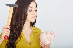 Young woman smashed piggy bank with a hammer Stock Photography