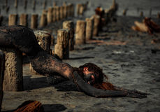 Young woman smeared with therapeutic mud and lies on wooden colu. Mn, next there is mud estuary. Spa Stock Photos