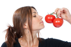 Young woman smell red tomatoes Royalty Free Stock Photography