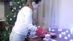 Young woman smelling the baked pie holding it with with gloves and putting it on table on background of Christmas stock footage