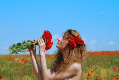 Young Woman Smelling a Bouquet of Poppies Stock Image