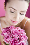 A Young Woman Smelling A Bunch of Pink Roses Royalty Free Stock Images
