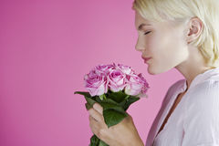 A Young Woman Smelling A Bunch Of Pink Roses Stock Image