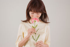 Young woman smelling flower. Young Asian woman smelling carnation flower Stock Photo