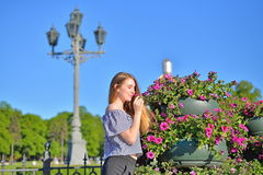 Young woman smelling flower in the flowerbed in front of an ancient lantern in St. Petersburg stock images