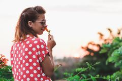 Young woman smelling flower in the garden Stock Image