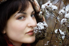 Young woman smelling flower with snow Stock Photo